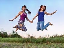 Duas meninas que saltam no ar que guarda as mãos Imagens de Stock