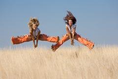Duas meninas que saltam no campo Imagem de Stock