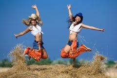 Duas meninas que saltam no monte de feno Fotos de Stock