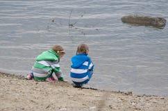 Duas meninas que sentam-se em um banco de rio Fotografia de Stock Royalty Free