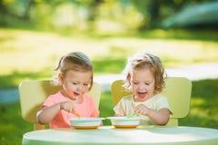 Duas meninas que sentam-se em uma tabela e que comem junto contra o gramado verde Imagens de Stock Royalty Free