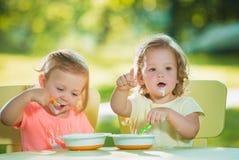 Duas meninas que sentam-se em uma tabela e que comem junto contra o gramado verde Fotografia de Stock