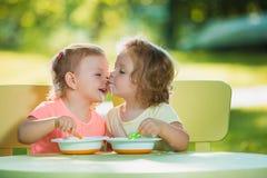Duas meninas que sentam-se em uma tabela e que comem junto contra o gramado verde Fotos de Stock Royalty Free