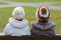 Duas meninas que sentam-se no banco no parque Imagem de Stock Royalty Free
