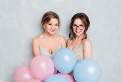 Duas meninas que têm o divertimento em um estúdio e que jogam com os balões azuis e cor-de-rosa A menina loura veste o vestido az foto de stock