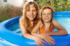 Duas meninas que têm o divertimento na piscina no dia ensolarado Imagem de Stock Royalty Free