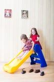 Duas meninas que têm o divertimento sobre a corrediça do campo de jogos Fotos de Stock Royalty Free