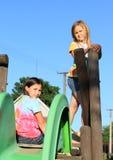 Duas meninas que têm o resto na corrediça Imagem de Stock