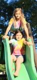 Duas meninas que têm o resto na corrediça Foto de Stock Royalty Free