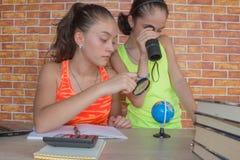 Duas meninas que trabalham em seus trabalhos de casa estudante atrativo novo Girls que estuda lições Fotos de Stock