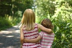 Duas meninas que vestem o braço da caminhada dos vestidos do verão no braço ao longo de uma floresta ensolarada arrastam fotos de stock royalty free