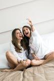 Duas meninas quentes que encontram-se em uma cama que toma uma foto dse com Fotografia de Stock