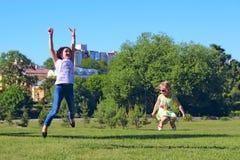 Duas meninas saltam acima no gramado Emoções criançolas Imagens de Stock