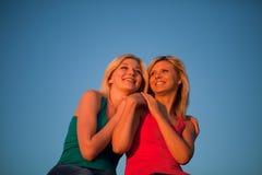 Duas meninas sentam o aperto e rir do céu azul foto de stock royalty free
