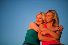 Duas meninas sentam o aperto e rir do céu azul foto de stock