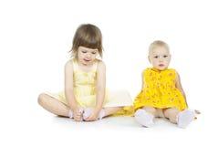 Duas meninas sentam-se fotos de stock