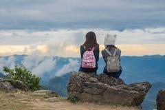 Duas meninas sentam-se em uma rocha que olha-se, o céu azul com nuvens e a opinião bonita das árvores verdes de cima no pha tung  imagem de stock