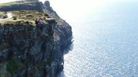 Duas meninas sentam-se na borda dos penhascos famosos de Moher na Irlanda vídeos de arquivo
