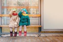 Duas meninas sentam-se na parada do ônibus Fotografia de Stock