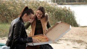Duas meninas sentam-se no banco de rio e abrem-se uma caixa em que uma pizza grande vídeos de arquivo