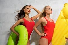Duas meninas 'sexy' com natação soam perto da parede ensolarada fotos de stock