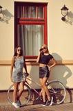 Duas meninas 'sexy' perto de uma bicicleta do vintage Fotografia de Stock Royalty Free