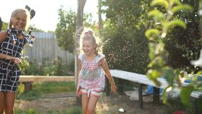 Duas meninas têm o divertimento que salta sob os córregos da água no verão na vila no jardim Feriados da rede filme