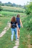Duas meninas vão em uma estrada de terra Viagem do verão no countryside_ foto de stock royalty free