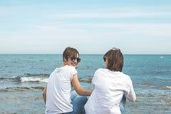 Duas meninas vestidas no branco pelo mar Mulheres com os óculos de sol na praia Imagem de Stock
