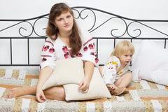 Duas meninas vestidas no ucraniano na cama Foto de Stock Royalty Free