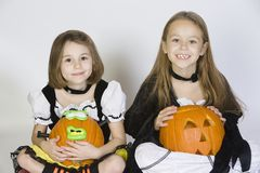 Duas meninas vestidas nos trajes de Dia das Bruxas que guardam Jack-O-lanternas Fotos de Stock
