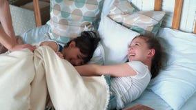 Duas mentiras bonitos pequenas das meninas na cama, no sorriso e no riso, movimento lento