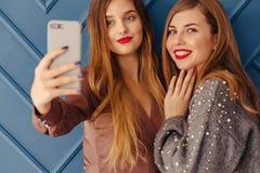 Duas moças à moda atrativas com o telefone no fundo simples do aqua fotografia de stock