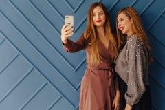 Duas moças à moda atrativas com o telefone no fundo simples do aqua fotografia de stock royalty free