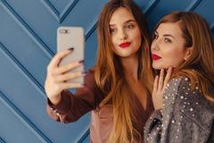 Duas moças à moda atrativas com o telefone no fundo simples do aqua imagens de stock royalty free