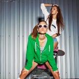 Duas moças bonitas jogam o trole do supermercado perto da parede Imagem de Stock