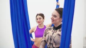 Duas moças desportivas estão levantando ao lado de uma rede azul da aptidão filme