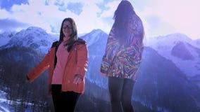 Duas moças escalam as montanhas no inverno Sorriso e ondulação Aprecie o feriado da montanha do inverno Tenha o divertimento no video estoque