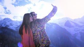 Duas moças escalam nas montanhas, fazem montanhas do selfie no fundo, sorrindo Aprecie a montanha do inverno vídeos de arquivo