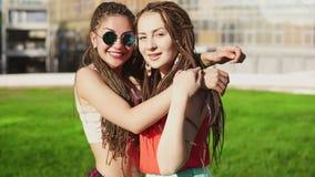 Duas moças felizes com temem abraçar-se Amigos fêmeas entusiasmado que abraçam-se e que riem durante video estoque