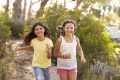 Duas moças felizes que correm em uma floresta, fim acima foto de stock royalty free