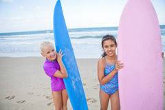 Duas moças felizes que guardam prancha na praia Fotos de Stock Royalty Free