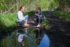 Duas moças ou amigas estão falando emocionalmente no parque Imagens de Stock