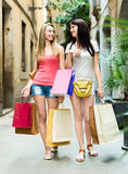Duas moças que andam e que discutem compras Imagem de Stock