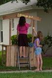 Duas moças que pintam um suporte de limonada imagens de stock royalty free