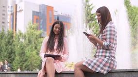 Duas moças que sentam-se em um parque perto de uma fonte usando um smartphone e uma tabuleta Movimento lento HD filme