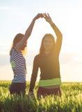 Duas moças que têm o divertimento no campo de trigo Foto de Stock