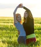 Duas moças que têm o divertimento no campo de trigo Fotos de Stock Royalty Free