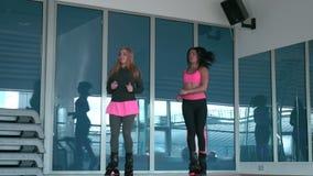 Duas moças que treinam em sapatas do kangoo no gym vídeos de arquivo