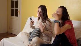 Duas moças sentam-se em casa no sofá, em um dia chuvoso olhando uma comédia, a fala e o riso Noite, casa, conforto filme